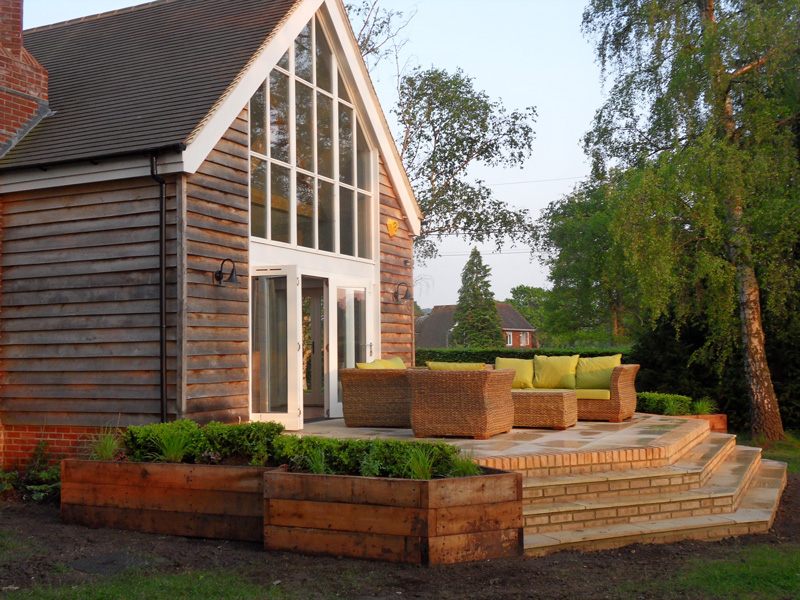 Raised outdoor seating aread and box plants in the Surrey garden