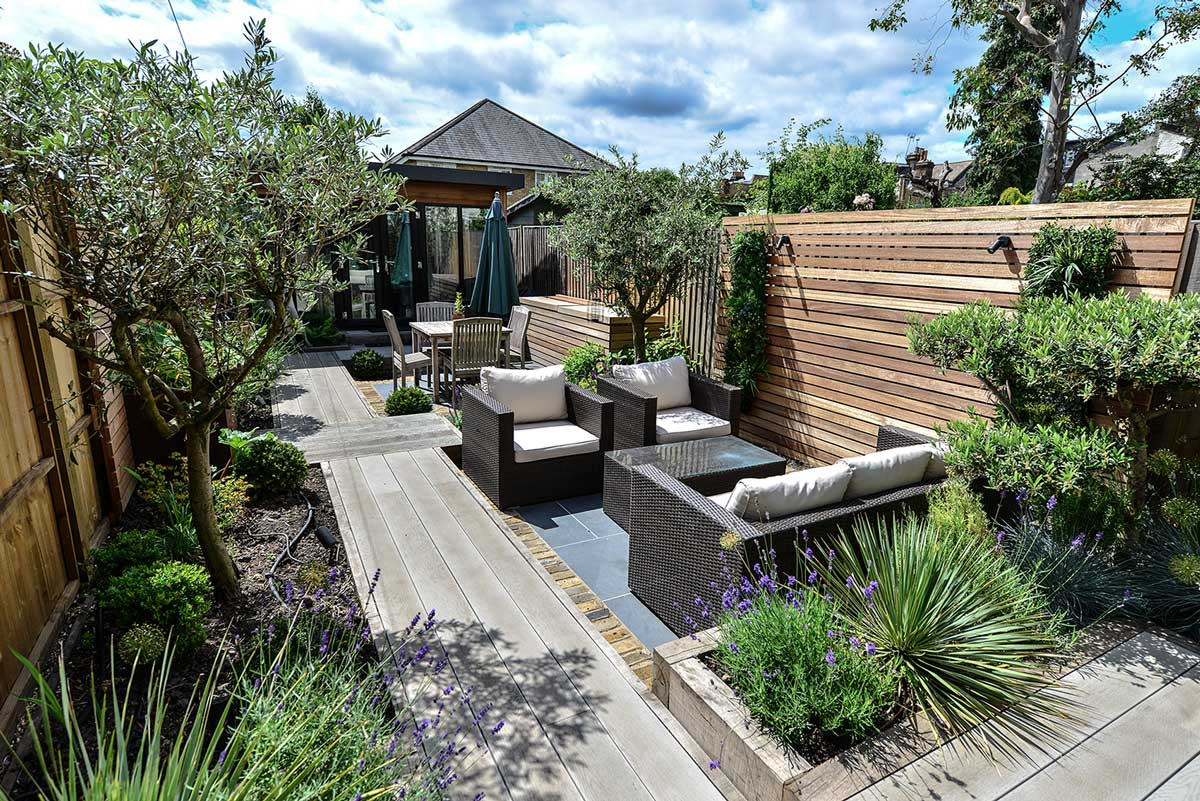 Seated area surrounded by sevreal planeted borders in this narrow town house garden in London